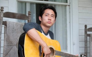 Glenn and a guitar...I think it's the same one Dale found in Season 2.  He's singing there's SPOILERS ahead, so stop reading if you don't want to know...